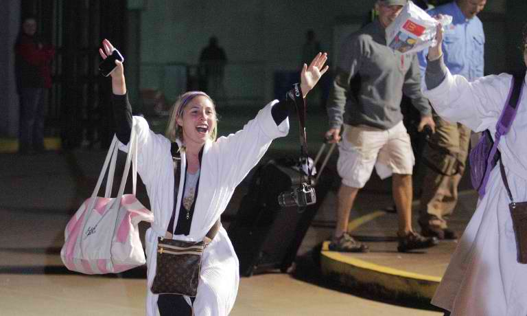 ROBED SURVIVOR.  Kendall Jenkins celebrates after stepping off the Carnival ship Triumph at the Alabama Cruise terminal in Mobile, Alabama, on February 14, 2013. The stricken Carnival cruise ship Triumph arrived back in port late February 14th, ending a nightmarish ocean voyage for some 4,000 desperate passengers and crew after it lost power over the weekend. AFP/Dan Anderson