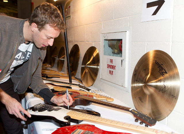 EVERY SIGNATURE HELPS. Coldplay's Chris Martin signs a guitar for the 121212 Concert auction. Photo from the official 121212 Concert Facebook page