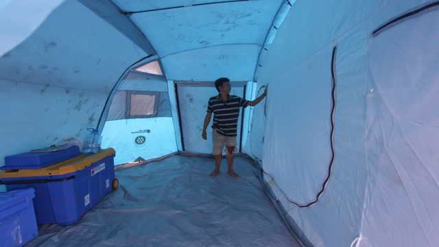 TEMPORARY HOME. 18-year-old Jason Gonzales tries to fix a temporary shelter after Pablo ripped through their home. Photo by Karlos Manlupig