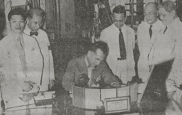 The Proclamation of the National Language being signed in the Presidential Study, Malacaan Palace. National Language Institute officials Cecilio Lopez (Tagalog), Jaime C. de Veyra (Samar-Leyte Visayan), Santiago A. Fonacier (Ilocano), Rafael Palma (Chairman of the National Council of Education), and Casimero F. Perfecto (Bicol), witness the signing.