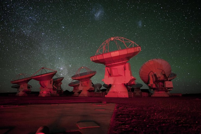 READY FOR USE. The Atacama Large Millimeter-submillimeter Array (ALMA) antennae bathed in red light. in the background there is the southern Milky Way on the left and the Magellanic Clouds at the top. ESO/C. Malin