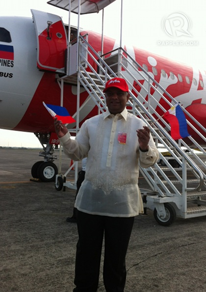 SEND OFF. AirAsia Group CEO Tony Fernandes waves Philippine flags infront of an AirAsia Philippines aircraft scheduled to fly to Kalibo, Aklan, at the tarmac of the Diosdado Macapagal International Airport, March 28, 2012. Photo by KD Suarez.