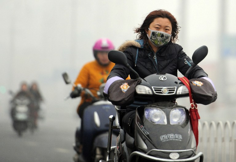 DRASTIC CHANGE NEEDED. A Chinese motorist wears a mask as she makes her way along a smog filled road in Hefei, east China's Anhui province on November 29, 2011. The amount of global warming gases sent into the atmosphere made an unprecedented jump in 2010, according to the US Department of Energy's latest world data on carbon dioxide emissions, with China alone was the biggest polluter with a spike of 212 million metric tons in 2010 over 2009. AFP PHOTO