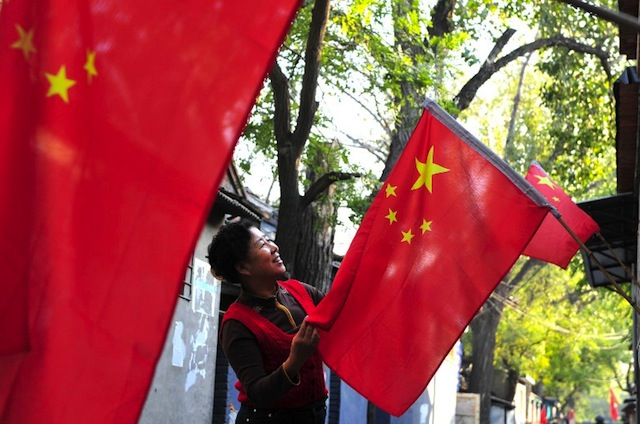 NATIONALISM. This picture taken on August 27, 2012, shows a resident hanging a Chinese national flag outside her home ahead of the 18th China Communist Party Congress in Beijing. AFP PHOTO