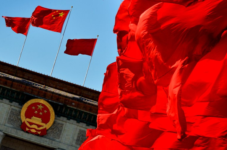 Chinese flags fly over the Great Hall of the People which is the site of the Communist Party Congress in Beijing on November 13, 2012. AFP PHOTO/Mark RALSTON