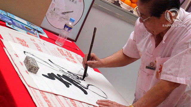CHINESE CALLIGRAPHY. A demonstration of intricate Chinese calligraphy enthralls passers-by in the atrium of Lucky Chinatown Mall