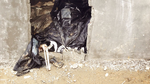 Bones stick out of a body bag in one of the newly-built crypts in New Bataan, Compostela Valley. Photo by John Javellana 25 Dec 2012.