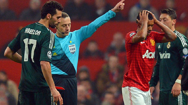 OUT. Manchester United's Portuguese midfielder Nani (R) holds his head as Turkish referee Cuneyt Cakir (2L) sends him off after a challenge against Real Madrid's defender Alvaro Arbeloa (L) during the UEFA Champions League round of 16 second leg football match between Manchester United and Real Madrid at Old Trafford in Manchester, northwest England on March 5, 2013. Photo by Andrew Yates/AFP