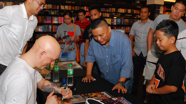 David Finch signs for Andrew E. as Fully Booked's Jaime Daez looks on, photo by Hub Pacheco