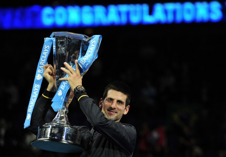 VICTORIOUS. Serbia's Novak Djokovic poses with the winners' trophy after the singles final against Switzerland's Roger Federer on the eighth day of the ATP World Tour Finals tennis tournament in London on November 12, 2012. AFP PHOTO / GLYN KIRK