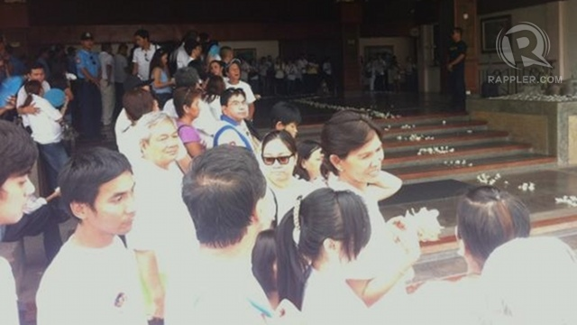Friends, relatives await Dolphy's coffin on the path to his burial site with flowers at hand. Photo by Natashya Gutierrez