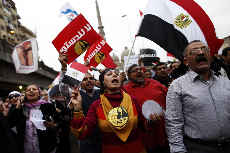 "PROTESTS. Egyptians, some holding up placards that reads in Arabic, ""No to the constitution"", and some shouting slogans march to the Egyptian Presidential palace to protest against the new constitution and Egyptian President Mohamed Morsi's decree on December 4, 2012, in Cairo.  AFP PHOTO/MAHMOUD KHALED"
