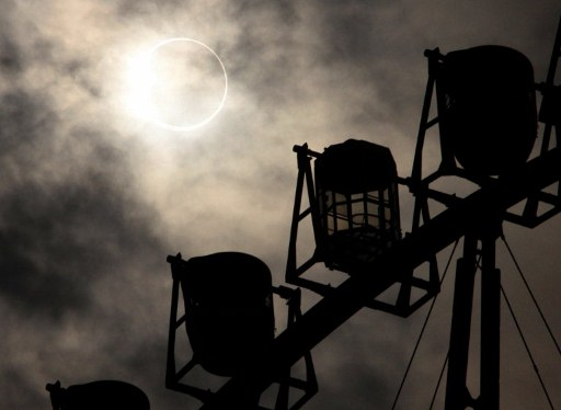 SOLAR ECLIPSE. An annular solar eclipse is seen over a ferris wheel in Tokyo on May 21, 2012. For the first time in 932 years, a swathe of the country was able to see the annular solar eclipse, when the moon passes in front of the sun, blocking out all but an outer circle of light. AFP PHOTO / Yoshikazu TSUNO