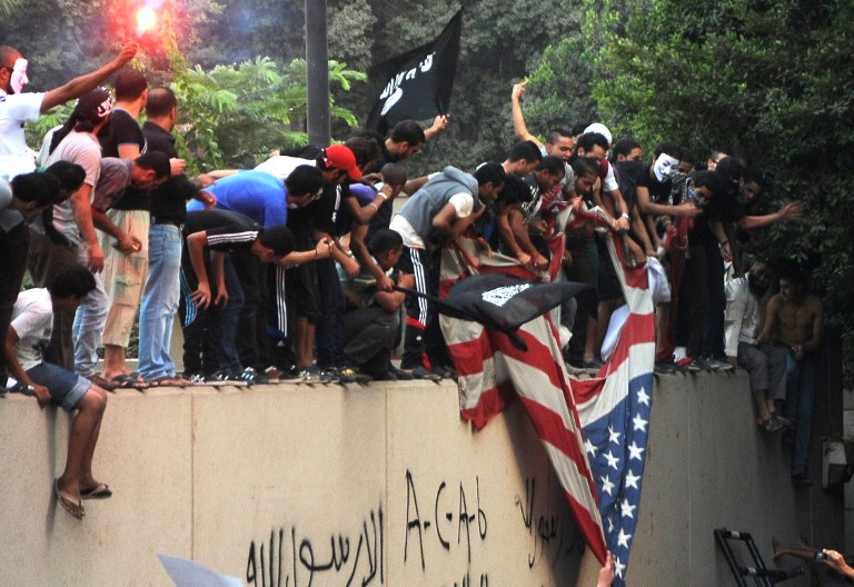 Egyptian protesters tear down the US flag at the US embassy in Cairo on September 11, 2012 during a demonstration against a film deemed offensive to Islam. AFP PHOTO