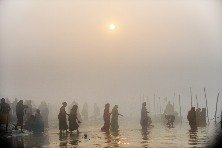 KUMBH MELA. Devotees walk into the waters at the Sangham or confluence of the Yamuna and Ganges river during day break at the Kumbh Mela celebration in Allahabad on January 13, 2013. AFP PHOTO/ROBERTO SCHMIDT