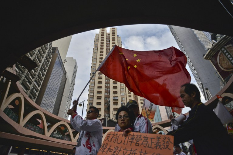 Marchers referring to themselves as supporters of Hong Kong and of the city's leader, Leung Chun-ying, walk with a Chinese flag though the streets of Hong Kong on December 30, 2012. AFP PHOTO / ANTONY DICKSON