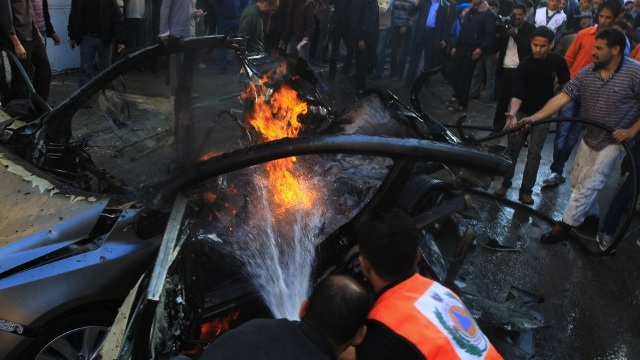 AIRSTRIKE AFTERMATH. Palestinian firefighters extinguish fire from the car of Ahmaed Jaabari, head of the military wing of the Hamas movement, the Ezzedin Qassam Brigades, after it was hit by an Israeli air strike in Gaza City on November 14, 2012. The top Hamas commander Ahmed al-Jaabari was killed in an Israeli air strike , medics and a Hamas source told. AFP PHOTO/MAHMUD HAMS