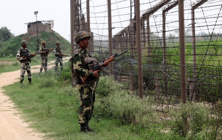 In this photograph taken on August 2, 2012 Indian Border Security Force (BSF) soldiers stand guard along fencing near the India-Pakistan Chachwal border outpost, some 65 kms north from the north-eastern Indian city of Jammu. AFP PHOTO/ STR /FILES