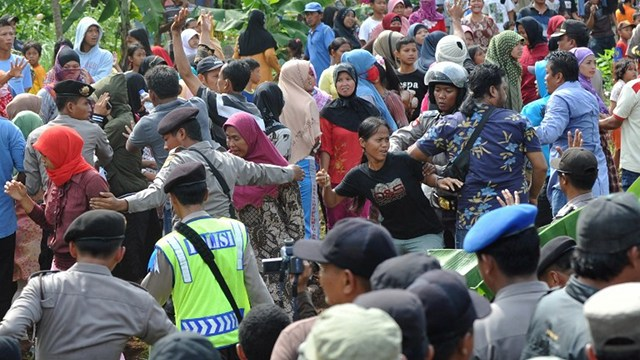 CHRISTMAS VIOLENCE. Indonesian police (C) block angry Muslim residents away from Christian worshippers from the Filadelfia Batak Christian Protestant intent on holding a Christmas mass on their property at the Jejalen Jaya village in Bekasi on December 25, 2012. Photo by AFP