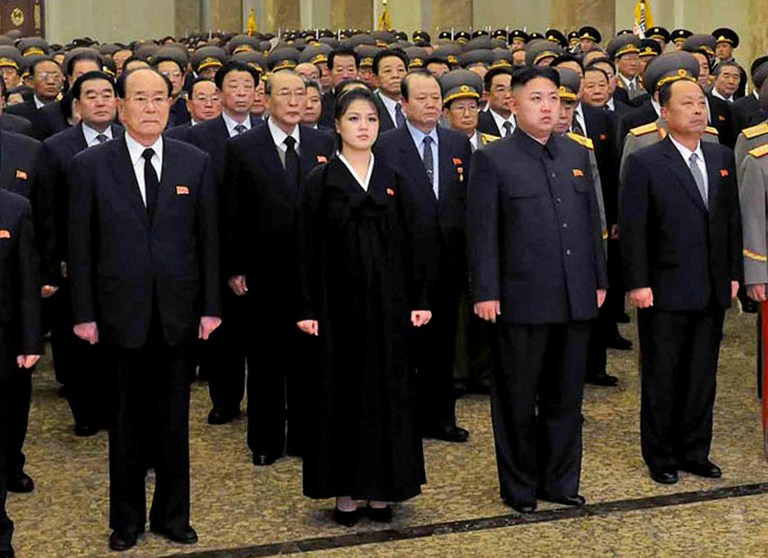 This picture taken by North Korea's official Korean Central News Agency on December 17, 2012 shows North Korean leader Kim Jong Un (centre R, front), accompanied by his wife Ro Sol Ju (centre L, front) and senior officials of the party and North Korean Army paying respect to late leader Kim Jong Il at the Kumsusan Palace in Pyongyang for the first anniversary of his death. AFP PHOTO / KCNA via KNS