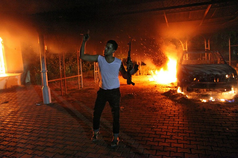 An armed man waves his rifle as buildings and cars are engulfed in flames after being set on fire inside the US consulate compound in Benghazi late on September 11, 2012. AFP Photo