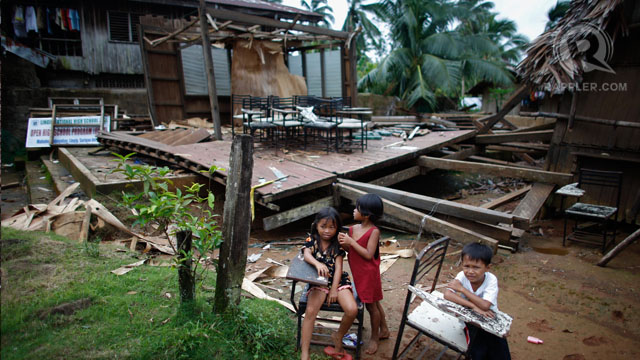 Students sit outside a shattered classroom in Mahayahay, Lingig, Surigao del Sur. 03 Jan 2013, Photo by John Javellana.