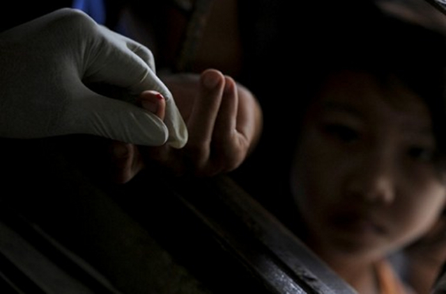 LONG-RUNNING BATTLE. Blood test on children at a clinic in Kanchanaburi province near the Thai-Myanmar border. Some Asian countries still in long-running battle against malaria, though deaths have declined. Photo by AFP