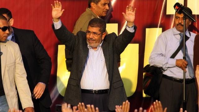 """DICTATOR"" MORSI? Egypt's Islamist President Mohamed Morsi waves to his supporters in front of the presidential palace in Cairo on November 23, 2012. AFP PHOTO/STR"