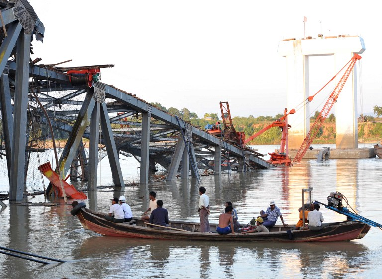 QUAKE AFTERMATH. People on a boat work near a damaged bridge in Kyauk Myaung township, east of Shwebo, following a powerful earthquake that hit Myanmar killing at least 13 people, injured dozens and sparking panic in the major central city of Mandalay on November 11, 2012. AFP PHOTO / Soe Than WIN