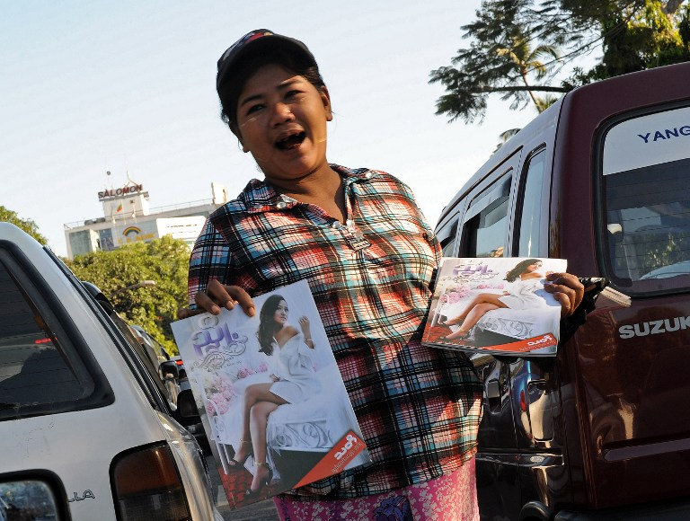 This picture taken on December 20, 2012 shows a Myanmar woman selling Myanmar's first sex education magazine in downtown Yangon. AFP PHOTO/ Soe Than WIN