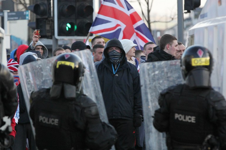 Police in riot gear try to contain with Union Flag waving loyalist protesters during clashes in east Belfast, Northern Ireland on January 12, 2013 after the latest loyalist march against the decision to limit the days on which the Union Flag would be flown over Belfast City Hall. AFP PHOTO / PETER MUHLY