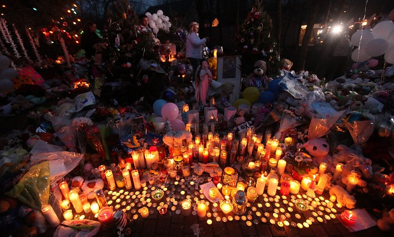 IN REMEMBRANCE. Candles are lit among mementos at a memorial for victims of the mass shooting at Sandy Hook Elementary School, on December 17, 2012 in Newtown, Connecticut. The first two funerals for victims of the shooting were held today. Mario Tama/Getty Images/AFP