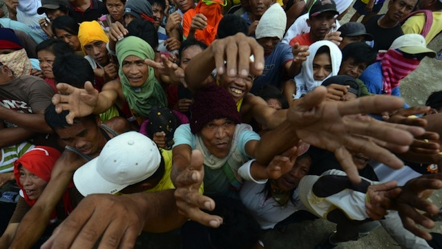 DESPERATE FOR AID. In this file photo, victims of Typhoon Pablo jostle for position as they beg for relief food being distributed by members of a private company in New Bataan, Compostela Valley on Dec 9, 2012. AFP photo