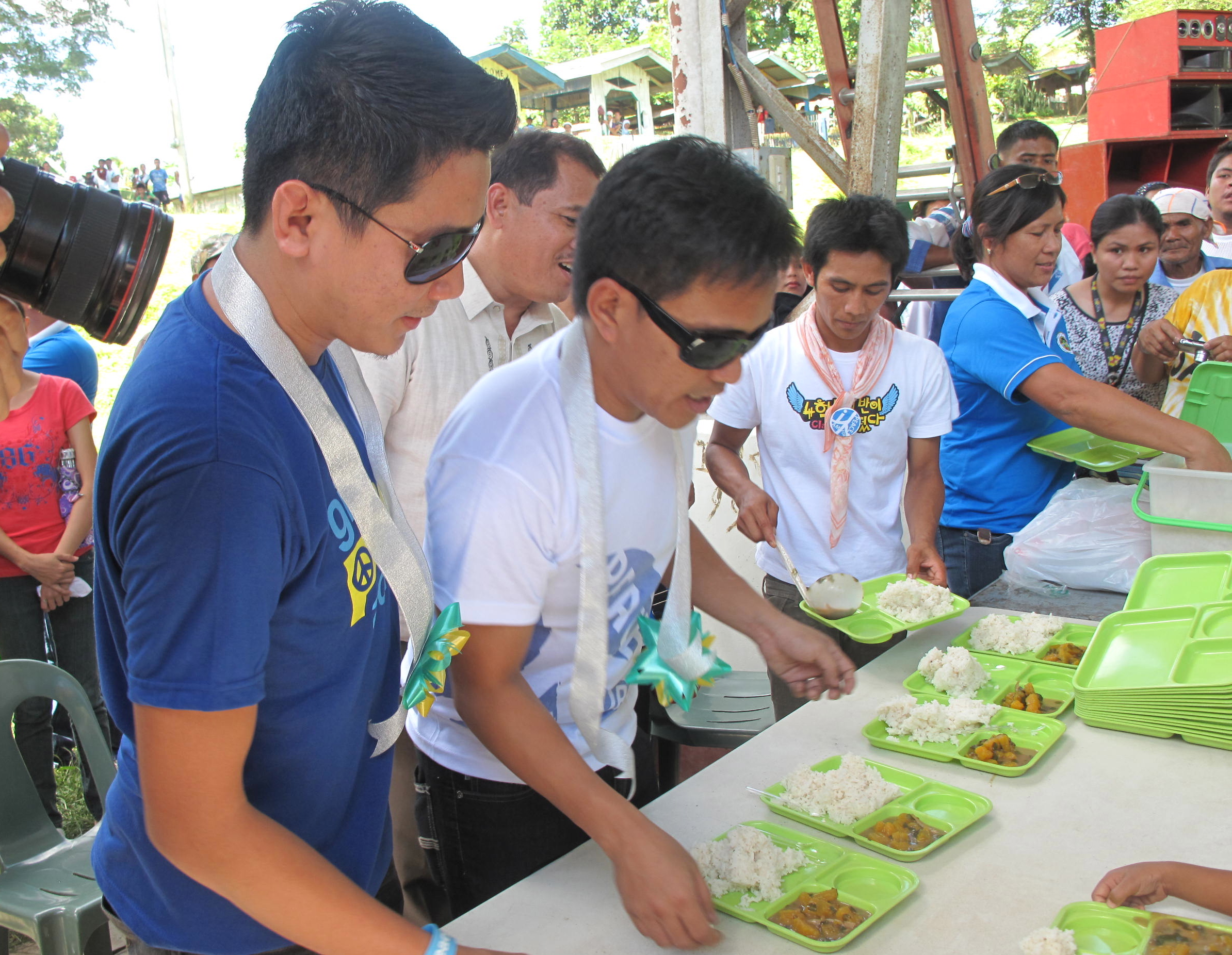 HELPING HANDS. Musicians Ebe Dancel and Datu Khomeni take part in a feeding program in Aleosan, North Cotabato. Photo by Angela Casauay.