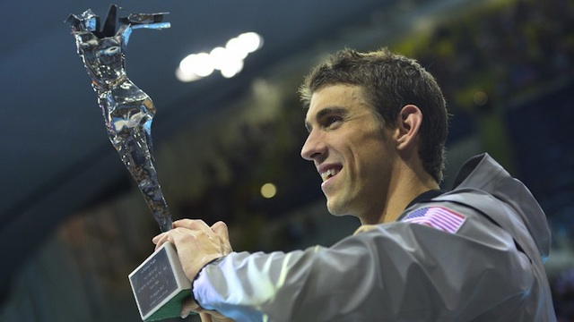 US swimmer Michael Phelps poses after he received the trophy of the greatest olympic athlete of all time after he won gold in the men's 4x100m medley relay final during the swimming event at the London 2012 Olympic Games on August 4, 2012 in London. AFP PHOTO / LEON NEAL
