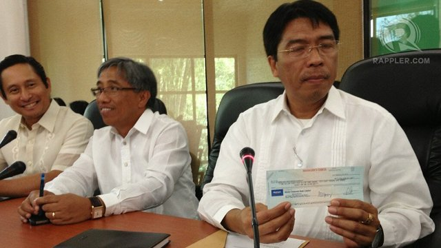 P1 BILLION. Mines and Geosciences Bureau chief Leo Jasareno (right) shows the check that Philex turned over to settle mine leak fine. Photo by Cai Ordinario