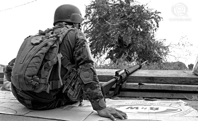 STILL WAITING. A PNP-SAF member waits at the Talon-Talon detachment, Sept.24, 2013. Photo by Paolo Villaluna