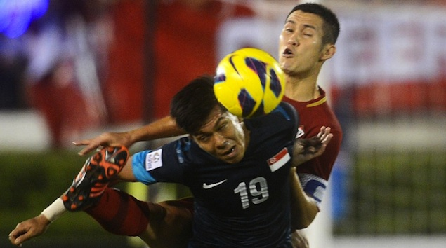 SUZUKI CUP. Thai football player Panupong Wongsa (R) battles for the ball with Mohammad Khairul Amari Kamal of Singapore (L) during their AFF Suzuki football Cup final second leg in Bangkok on December 22, 2012. Photo from AFP