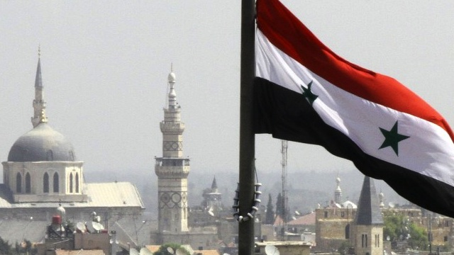 The Syrian flag flutters above Damascus on September 20, 2012. AFP PHOTO/LOUAI BESHARA