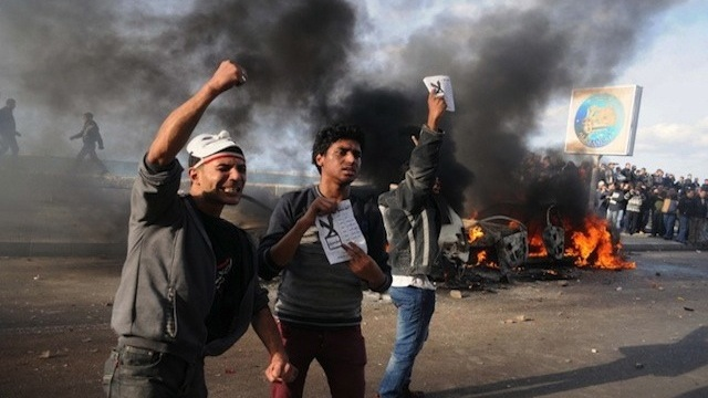 "CLASH. Egyptian protesters shout slogans in front of burning cars set on fire during a demonstration calling for a ""No"" vote in a referendum on a new constitution in Alexandria. AFP Photo"