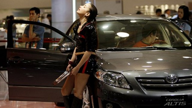 NO REST. This model takes a break during a car show, but consumers are buying more. Photo by AFP