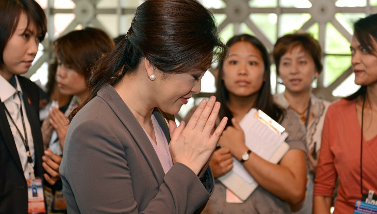 Thai Prime Minister Yingluck Shinawatra (C) joins her hands in a traditional greeting as she arrives at the parliament in Bangkok on November 28, 2012. AFP PHOTO / Christophe ARCHAMBAULT