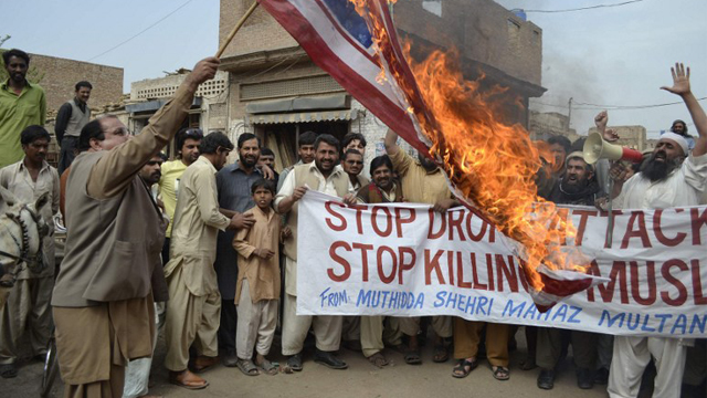 PAKISTAN, Multan : Activists of Pakistan Muthidda Shehri Mahaz burn the US flag during a protest in Multan on March 14, 2012, against US drone attacks. A US drone strike in Pakistan's lawless tribal belt on March 13 killed eight fighters supporting the Taliban in Afghanistan but not hostile to Pakistani authorities, local officials said. AFP PHOTO/S S MIRZA