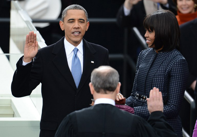 SECOND TERM. US President Barack Obama takes the oath of office during the 57th Presidential Inauguration ceremonial swearing-in at the US Capitol on January 21, 2013 in Washington, DC. The oath is administered by US Supreme Court Chief Justice John Roberts, Jr. Obama is joined by US First Lady Michelle Obama. AFP PHOTO/Emmanuel Dunand