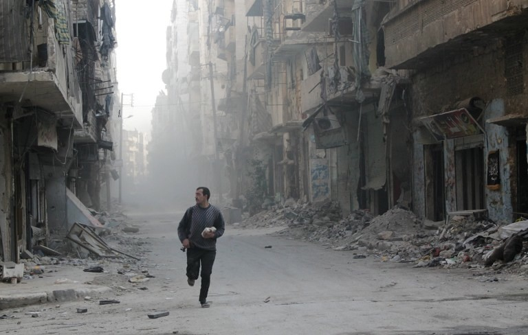 RUNNING FROM DANGER.  A rebel fighter from the Free Syrian Army runs in a street of Aleppo's Salah al-Din neighborhood during fighting against Syrian government forces on November 18, 2013. AFP / Karam al-Masri