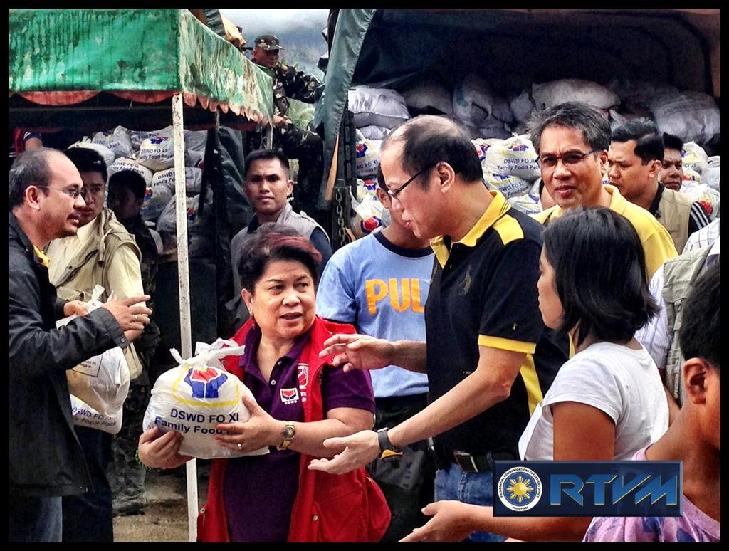 RELIEF OPERATIONS. President Aquino hands out relief goods with Social Welfare Secretary Dinky Soliman in Compostela Valley. Photo from RTVM