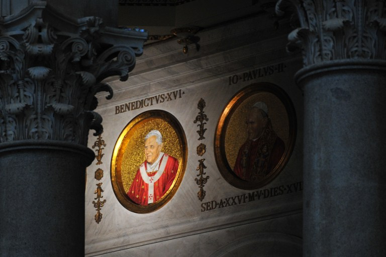 The portrait of Pope Benedict XVI (L) is displayed next to Pope John Paul II's on a wall of the St Paul Outside the Walls' basilica on February 13, 2013 in Rome. The portraits of each pope are displayed in a frieze extending above the columns separating the four aisles and naves. AFP PHOTO / TIZIANA FABI