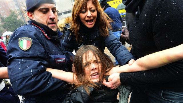 'BASTA BERLUSCONI' A topless feminist is arrested by riot policemen outside the polling xtation where former Prime Minister Silvio Berlusconi casted his ballot on February 24, 2013 in Milan. AFP PHOTO / GIUSEPPE CACACE