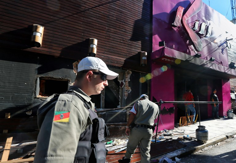 Policemen check the Kiss nightclub where a blaze on the eve killed more than 230 people, on January 28, 2013 in Santa Maria, southern Brazil. AFP PHOTO / JEFFERSON BERNARDES