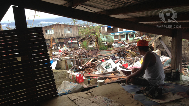 A resident looks out a makeshift roof built atop his house that was severely damaged by typhoon Bopha, locally known as &quot;Pablo&quot;  in the town of Cateel, Davao Oriental December 31, 2012. Thousands of residents dependent on aid and relief to sustain themselves are currently struggling to rebuild their homes and livelihood that were devastated by the typhoon which made landfall last December 4, 2012. Photo by John Javellana.
